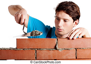 Man building a wall - Focused man building a brickwall with...