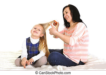 Young beautiful mother with hairbrush brushing daughter...
