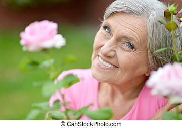 Woman with pink flower - Happy older woman with pink flower