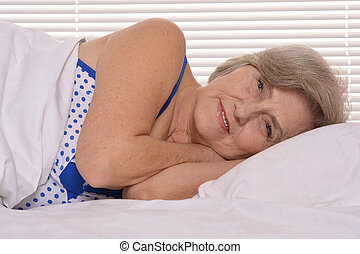 Attractive older woman resting in the bedroom - Beautiful...
