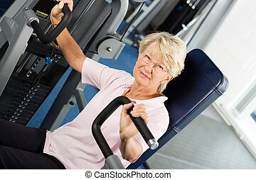 Older woman working out at the gym