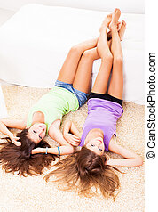 Leisure time - Two Beautiful teenage girls lying on the...