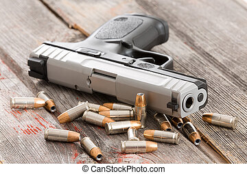 Handgun with scattered bullets and cartridges - Close up...