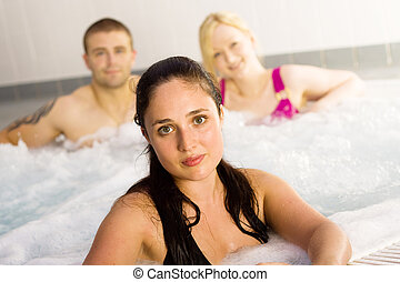 Friends in the jacuzzi - A group of three friends in sports...