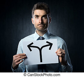 Taking decisions - Man holding a sign with directions and...