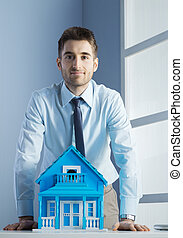 Real estate agent with model house - Young real estate agent...