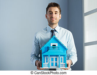 Real estate agent with model house - Friendly real estate...