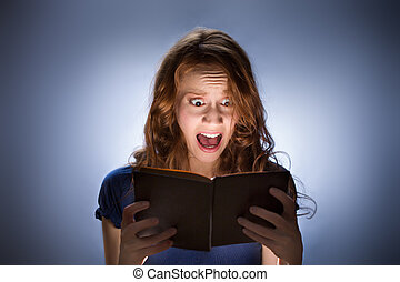 Woman reading horror book nad screaming - Concept shot of...