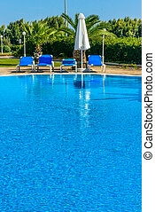 swimming pool with sun loungers - deck chairs under a canopy...