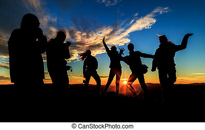 Silhouettes on the sunset - Young happy people silhouettes...