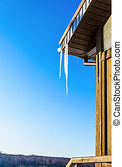 roof of the house with hanging icicles on blue sky...