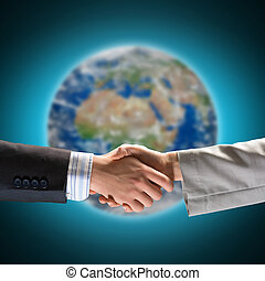 handshake of two businessmen on the background of the planet...