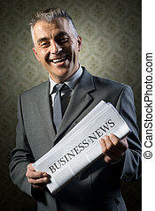 Businessman holding newspaper - Handsome businessman holding...