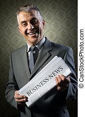 Businessman holding newspaper - Handsome businessman holding...