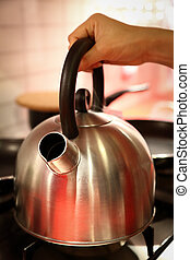 Women hold modle kettle in kitchen room.
