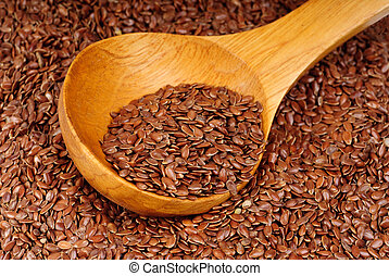 close up of flax seeds and wooden spoon as food background