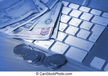 online transaction concept - dirhams on top of keyboard