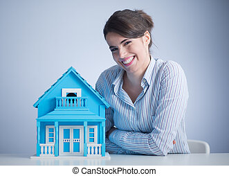 Real estate agent - Beautiful woman at desk with light blue...