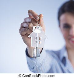 Holding out house keys - Real estate agent holding out house...