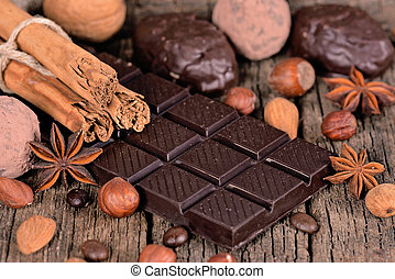 Dark chocolate with spices on a wooden surface