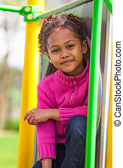 Portrait of a cute african little girl at playground -...