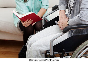 Caregiver reading a book to her pensioner on wheelchair