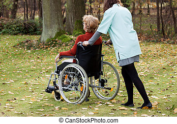 Carer on a walk with patient - Carer walking in the park...