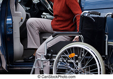 Disabled driver - Handicapped elder woman getting into a car