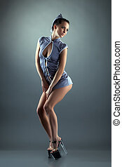 Cute young girl posing in erotic stewardesses suit, on gray...