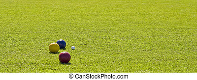 Balls on Green Grass - Bocce balls on a green grass lawn