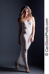 Charming model posing in skin-tight negligee, on gray...