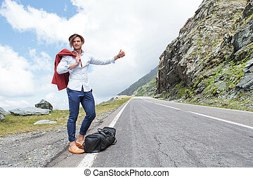 young fashion man hitchhikes with joy - portrait of a young...