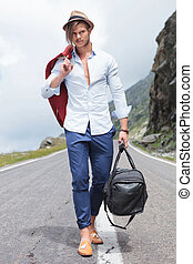 young man walking with bag on the road - full length photo...