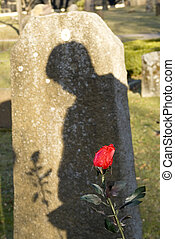 man standing by the grave mourning - shadow of a man...
