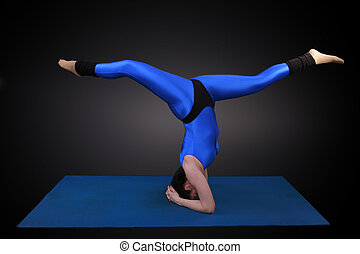 Headstand balancing act - Woman doing yoga, Headstand...