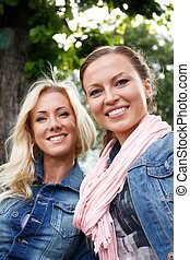 Two beautiful smiling young women in jeans jackets sitting...