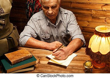 Senior writing letter with quill pen in homely wooden...