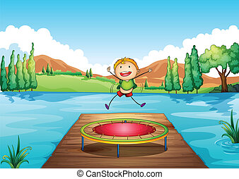 A boy playing with the trampoline at the river -...