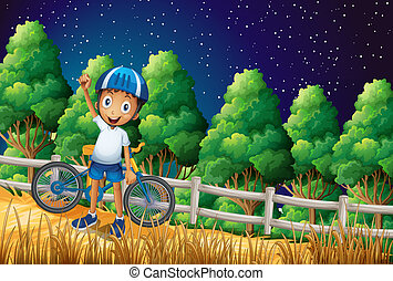A happy boy with a bike standing at the woods near the fence...