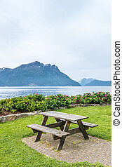 Table and benches for picnic on fjord shore, Norway