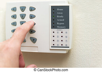 Home alarm system - Hand is setting home security alarm...