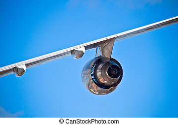 Airplane wing and turbine and a blue sky
