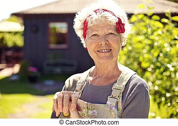 Active senior woman standing in backyard garden