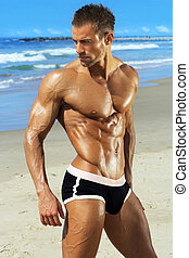 Male fitness model - Gorgeous muscular young man at beach