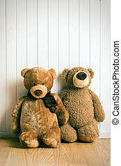 teddy bears in front of  old wooden wall