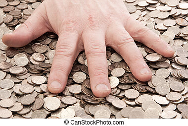 greed - human hand and a pile of coins cents