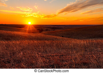 Orange glow of a sunset in Kansas Flint Hills - A view of...