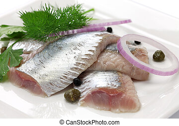 pickled herring, cold appetizer on white dish