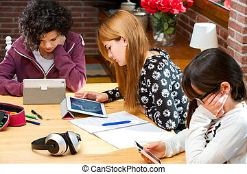 Three students working on digital devices - Threesome female...