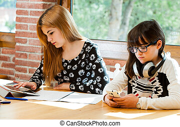 Two girls concentrating with schoolwork - Two young girls...